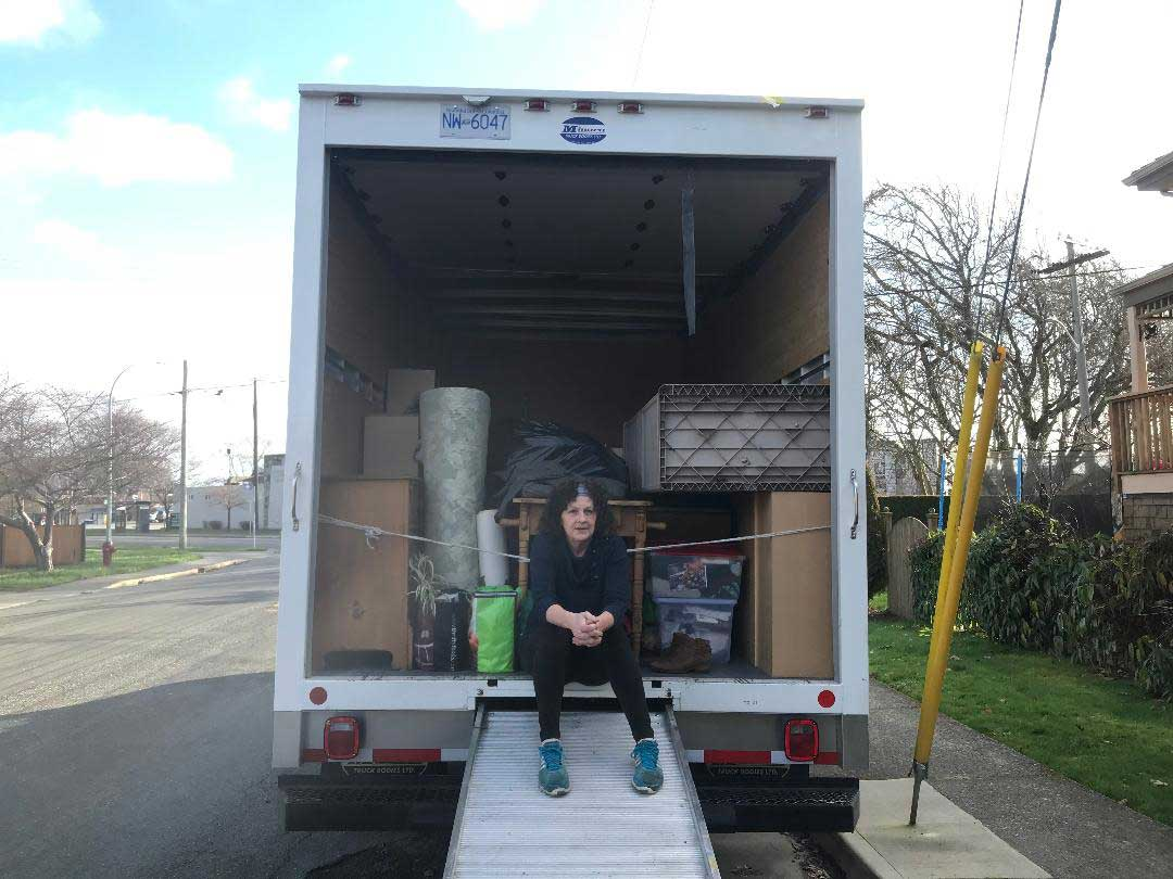 Lynne sitting on the back of a partially full moving truck