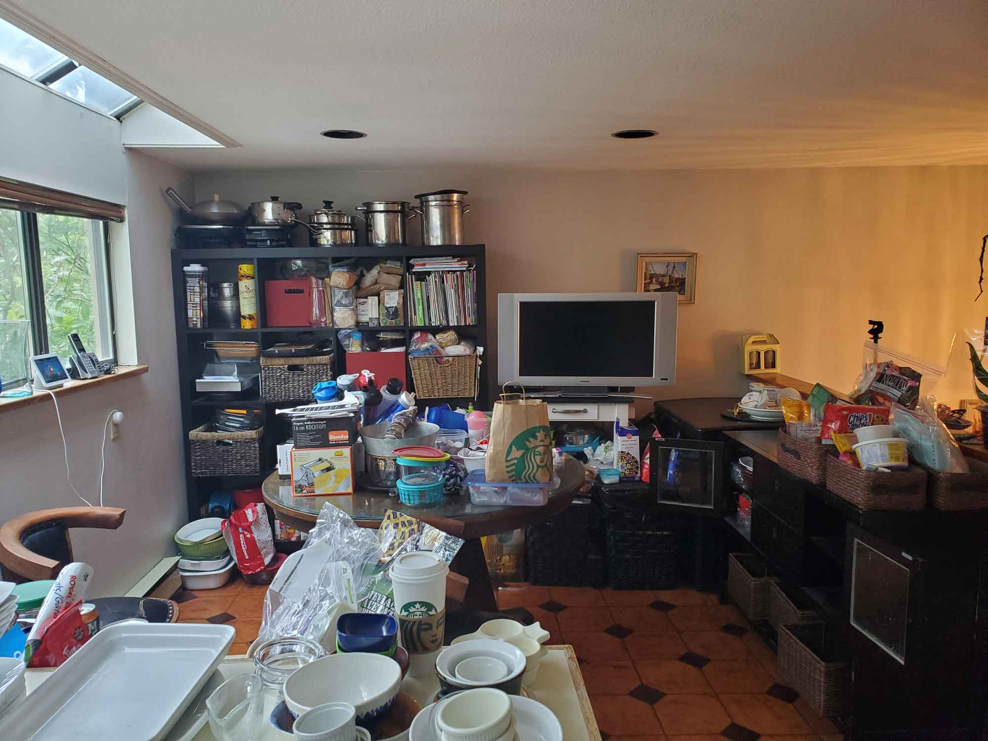 Kitchen table and counters full of items making them inaccessible