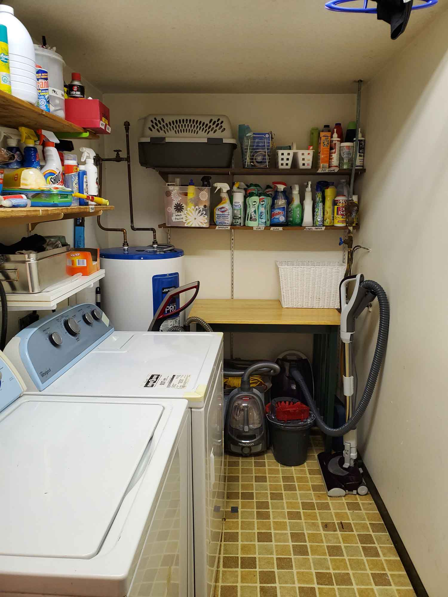 A laundry room with the side table, dryer and floor space cleared except for essential items