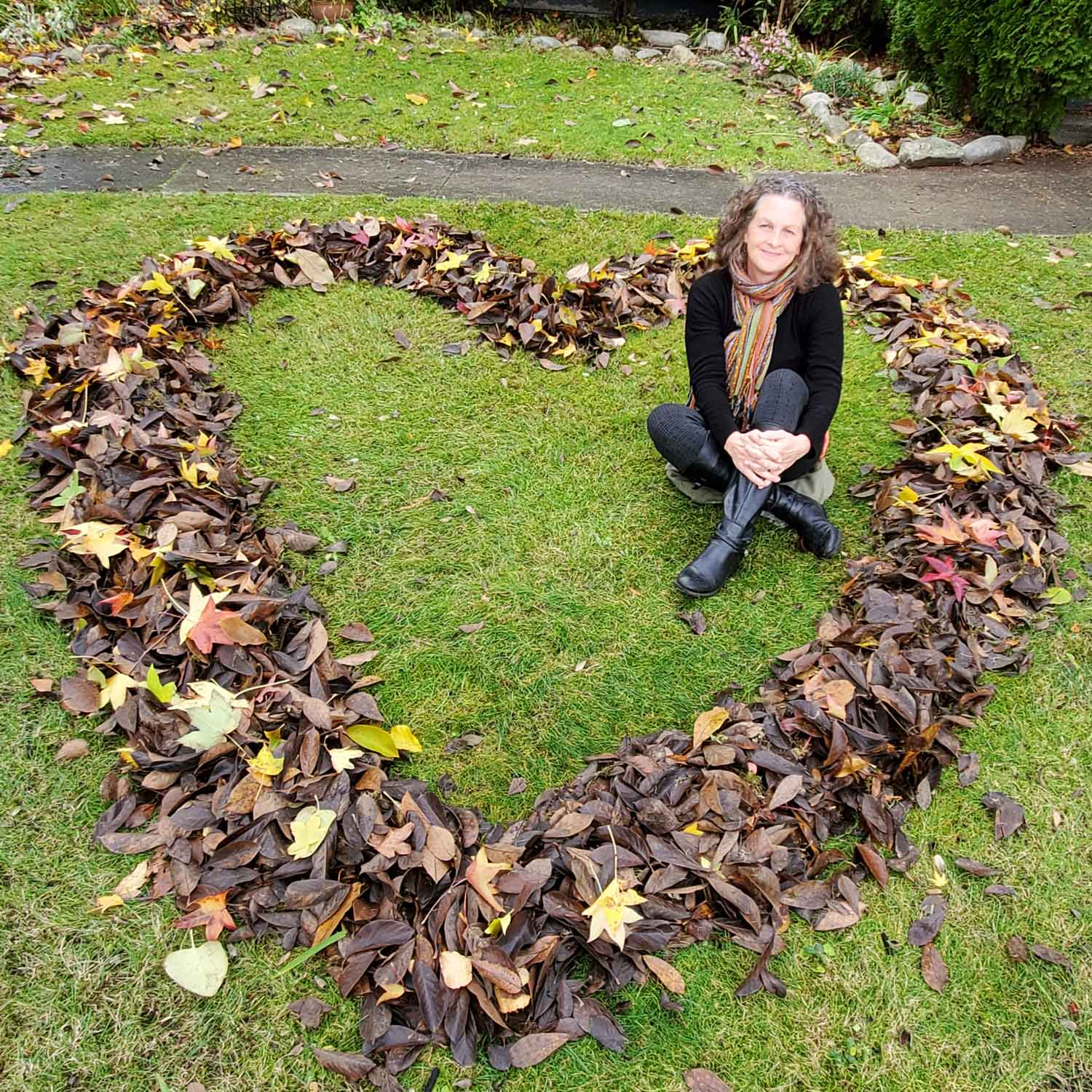 Lynne Jamieson smiling at the camera sitting inside a heart made of leaves